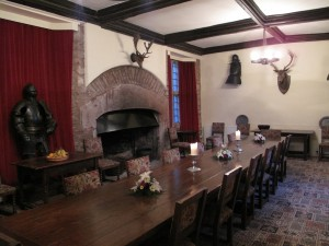 A large wooden dining room table in a hall with a big fireplace and an ancient suit of armour