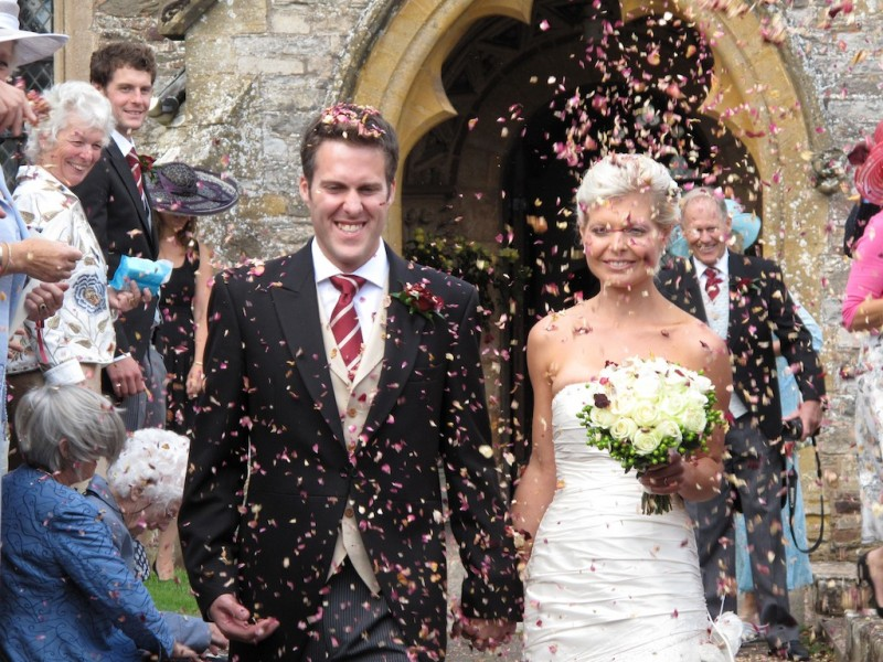 Emily and Ben, bride and groom, in a shower of confetti outside a church