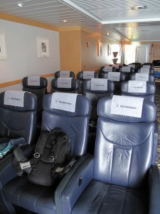 Several rows of single reclining chairs in a large cabin on a boat