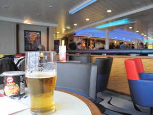 A tub of Pringles and a pint of beer on a table in the ship's bar