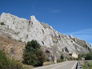 The road leads to a lone chapel in front of a cliff under blue skies