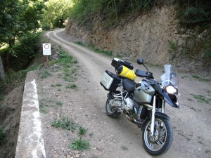 Bike emerges from a dirt track down a hill, no entry sign in background
