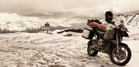 Bike parked in snow on the Col de la Bonette, sign in background points to Nice