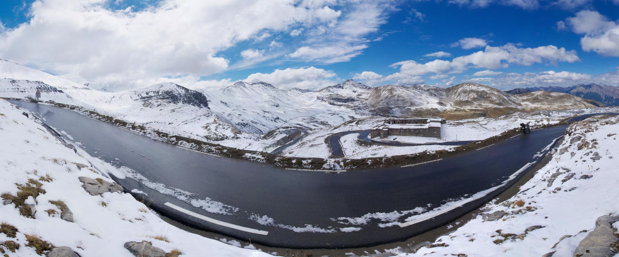 Wide panorama takes in snowy road to Col de la Bonette under blue skies and fluffy clouds