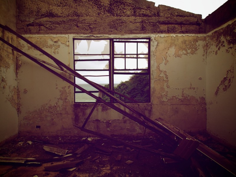 Ironwork from a missing roof partially obscures a broken window overlooking a beach scene