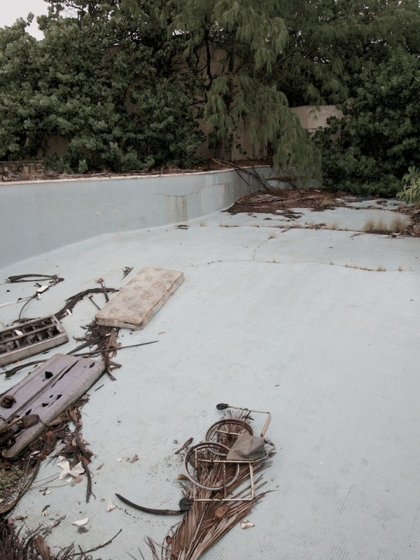 A broken wheelchair adds to the detritus at the bottom of a disused swimming pool