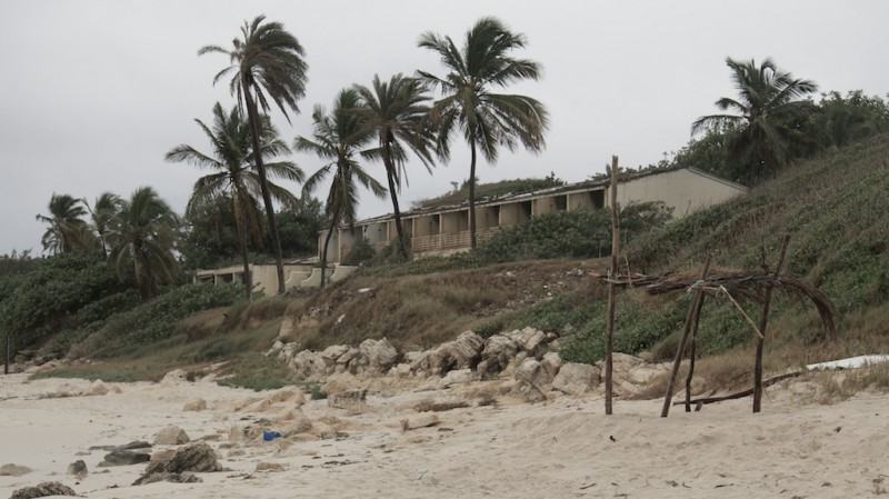 A derelict building looks out onto a beach amidst stormy weather