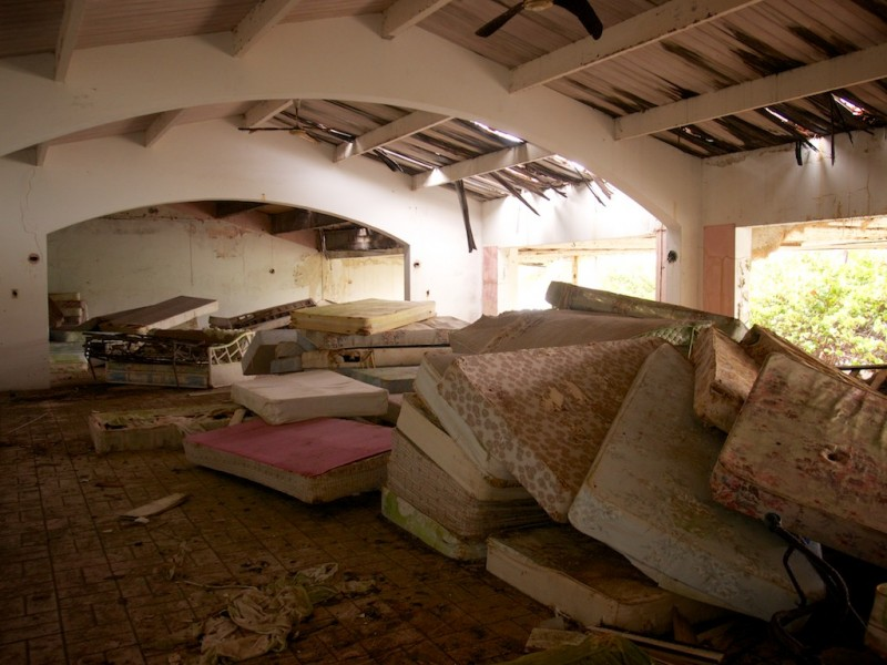 Dirt mattresses are piled untidily in large piles in a big room whose roof shows signs of wind and rain damage