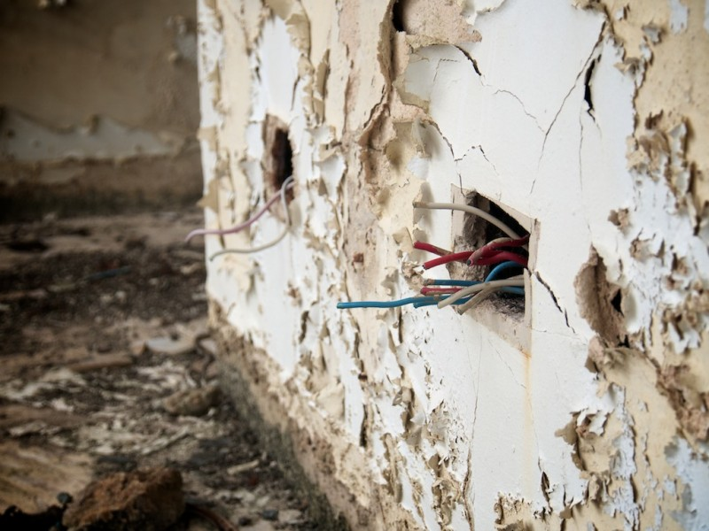 Wires protrude from a wall of crumbling paint where a socket used to live
