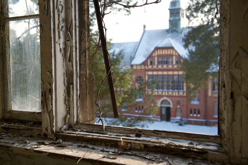 Looking past the decaying window panes from an upper floor at another building across the yard
