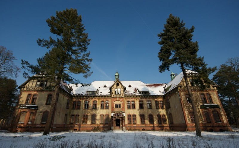 Wide angle shot of a majestic building, slowly crumbling in the snow