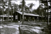 A low wooden building standing amongst trees