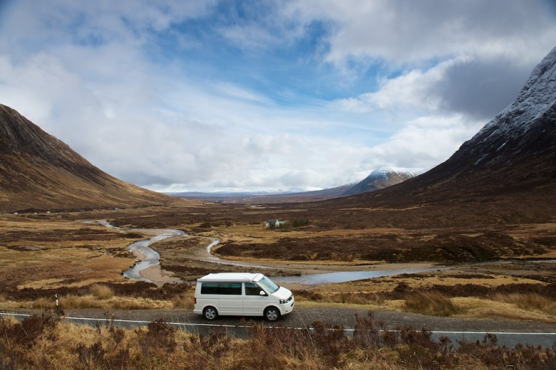 A lone camper van parked by the side of the road in a picturesque valley, gentle mountains frame the pale blue sky either side