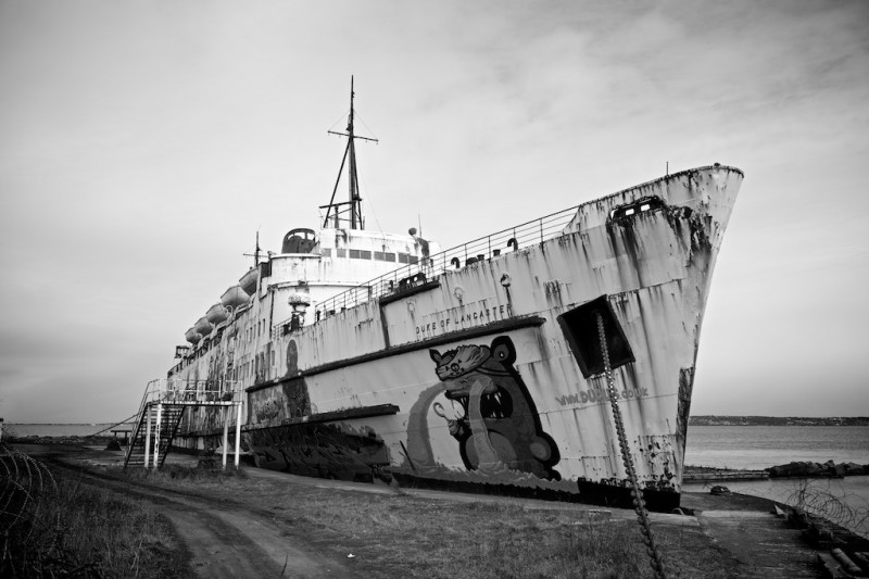Black and white photo of a derelict, rusting ocean liner moored at a lonely dock, covered in graffiti