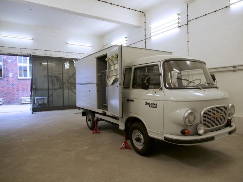 A pristine Barkas B1000 Transporter stands inside a garage, the doors o the body at back open