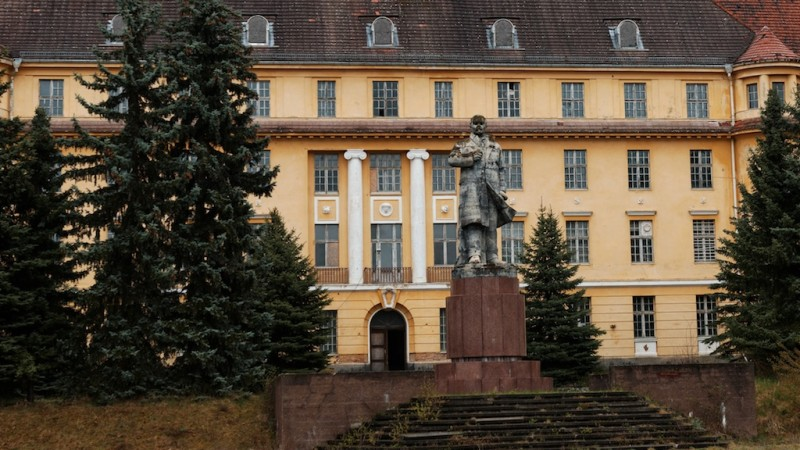Statue to former Soviet hero with his hand on his chest in front of imposing building