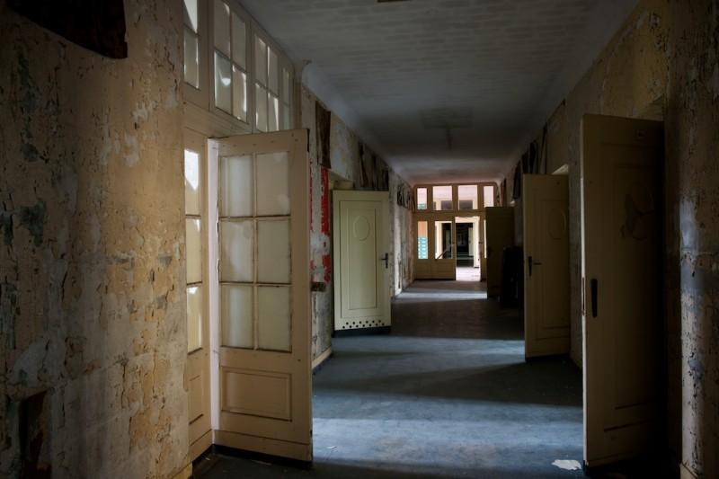 Traditional urbex shot showing forlorn doors opening onto paint-peeling corridor