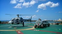 A white and blue helicopter is being refuelled on a sunny helipad under a blue sky