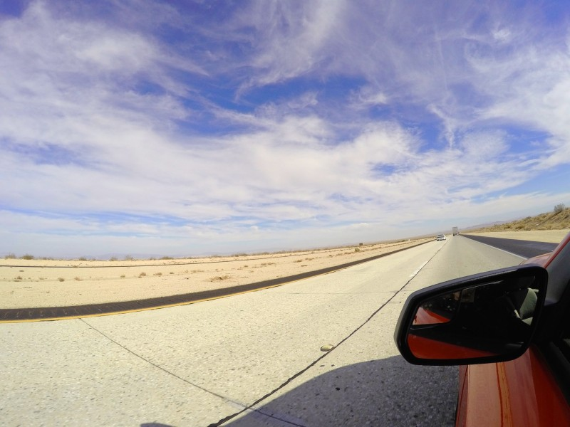 View from the side window of a car at Californian interstate stretching away into the distance under blue skies