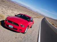 Arty-farty shot of a red sportscar parked by the side of a very long, straight desert road