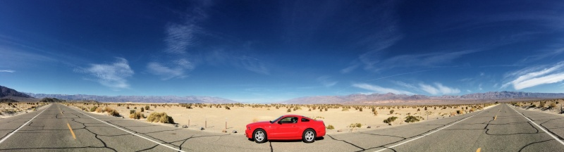 Panorama shot of - you guessed it - a red sportscar on a very long desert road