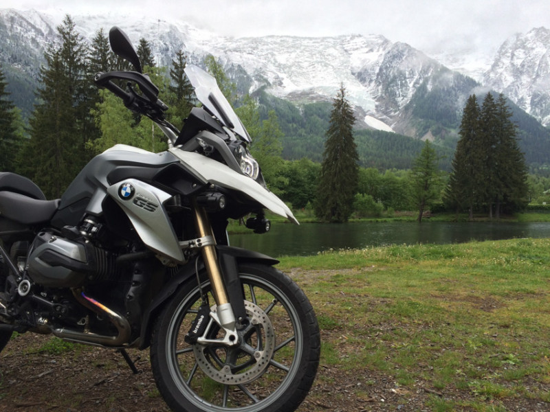 Close-up shot of black and white BMW motorbike in front of some snow-covered mountains