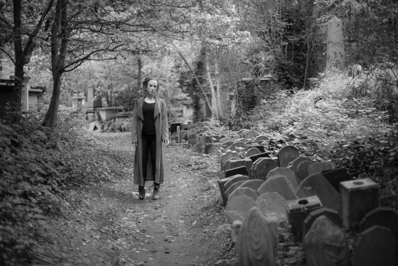 Black and white photo of a girl standing on a tree covered avenue lined with lots of small tombstones