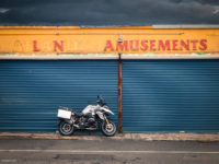 Bike parked in front of shuttered amusement arcade, rusty signage and totally realistic clouds in background.