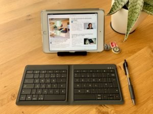 Photo of a wooden desktop showing an iPad and a bluetooth keyboard made by Microsoft