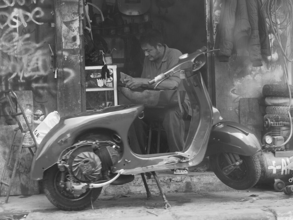 Monochrome photo of a guy fixing a scooter in a tiny roadside workshop