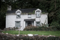 Front view of a derelict dwelling in front of which stands a sign bearing the words Rock Cottage