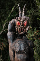 Image of a wooden carved figure with glowing red eyes and the horns of a goat